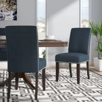 Chic and sophisticated, this parsons chair is an effortlessly on-trend seating option for your dining ensemble. Founded on a solid wood frame, this dapper design strikes a glamourous parsons style silhouette with a high back, thick seat, and four tapered square legs in a rich espresso finish. Available in a curated selection of fashionable colors to best suit your tastes, brushed polyester suede upholstery ensconces the seat, accented with tin nailhead trim in a pewter finish, and padded with...