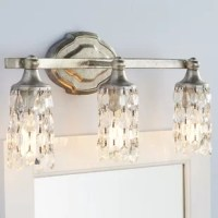 Light your bathroom in glamorous style when you add this three-light vanity luminary to your space. Sure to make a statement in the smaller space, this lovely light showcases three bell-shaped shades that are draped with strings of detailed glass crystals. It is available in different metallic finishes, so you can find the perfect hue for your home. It supports three 60W medium base bulbs, which are not included with this vanity light.