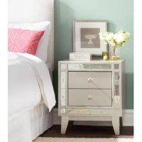 A brilliant reflection of your glamorous style, this splendid two-drawer nightstand lends luxurious elegance to your bedroom ensemble. Made from solid poplar in a metallic mercury finish, this enchanting design showcases a simple rectangular silhouette, bejeweled hardware, and chic etched mirror plating. Each drawer features full extension glides—ideal for stowing away a notepad, flashlight, pajamas, and your spare pair of reading glasses, while the smooth surface provides a perfect platform...