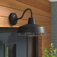 Shine a light down on any alfresco outdoor arrangement with this versatile barn light; an industrial design that's suited for damp locations, such as covered patios and porches. Crafted of metal, this textured black-finished fixture features a round backplate and a curling arm that supports a schoolhouse-shaped metal shade. Integrated LED technology provides brightness equivalent to one 60 W bulb without the worry of replacing light bulbs, while a removable chrome-finished cage completes the...