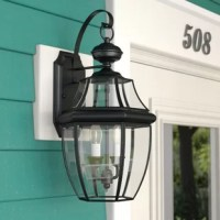 A classic design gets a contemporary refresh with this two-light outdoor wall lantern. Rated for use in wet locations, this metal fixture features a geometric backplate, a curling arm, and a curved silhouette in a versatile solid finish. Clear glass panels make up the shade, rounding out the look with a sleek touch as they provide a peek at a pair of candelabra-base bulbs (not included) staged within. Installation is required.