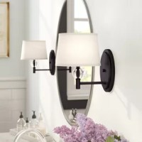 Whether illuminating the bathroom vanity mirror or casting light over a nightstand in the master suite, this one-light armed sconce lends tasteful traditional style to any space in your home. Available in a curated selection of classic finishes, the backplate strikes a molded circle silhouette, while a short, straight arm suspends the tiered light holder in place. Rounding out the design, a transparent crystal ball accent, the holder, while a white fabric tapered drum shade diffuses soft light...