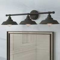 Industrial style abounds with this vintage-inspired armed wall sconce. Spanning just under 30 inches wide, this fixture features a round backplate and a horizontal rod that disperses its three lights. Its bowl-shaped metal shades help diffuse this luminary's brightness without completely covering its lightbulbs, while a versatile oil-rubbed bronze finish completes the design with a touch of rustic character. It accommodates three A19 medium-base LED 60 W lightbulbs (not included), and is...