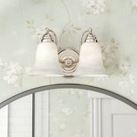 A romantic twist on a traditional, this vanity light is sure to make any master suite mirror or guest room sink space shine. A pair of faux alabaster glass bell shades gently diffuse light while scrolling arms reminisce on styles of years past. Measuring 8'' H x 12'' W, this luminary is on the smaller side, but always makes a statement. The manufacturer for this product provides a one-year warranty.