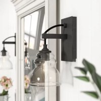 Blending the sleek lines of contemporary style with this rustic charm of cottage aesthetics, this armed sconce is a perfect pick for your modern farmhouse look. The glass shade has a rounded design that is reminiscent of antique designs for added flair.