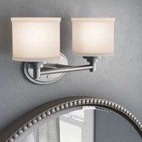 Perfect for illuminating petite powder rooms, this two-light vanity light brings a touch of traditional style as it brightens your space. Suitable for damp locations, this clean-lined metal fixture features an oval backplate with two arms and a horizontal rod that stretches 15 inches wide to support a pair of lights. White cylindrical glass shades complete the classic look, helping to diffuse this luminary's light upwards. It accommodates 60 W incandescent bulbs (not included).