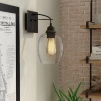 Don't settle for simple lighting if you want a bolder look? To complement your industrial ensemble, try adding this armed sconce. Inspired by antique designs, it showcases a round seeded glass shade, which lets the 60W E26 Medium base bulb (not included) shine brightly over your space. The rectangular backplate and sleek rounded arm are crafted from metal with a dark finish. This light is hardwired and suitable for the bathroom.