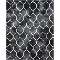 Transform a cozy seating ensemble into a bohemian-inspired living room look with this eye-catching handmade rug, featuring a dip-dyed design and a trellis motif in graphite and ivory.