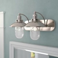Bring sleek sophistication and a bright glow to your bathroom ensemble with this elegant vanity light. Blending vintage-inspired design with a touch of contemporary style, it showcases a streamlined stainless steel frame with arching arms and an oval backplate. At the end of each arm are a shallow bowl shade and clear glass dome cover which encase the 60-watt bulbs (not included). With a brushed nickel finish, it adds a crisp touch to your look.