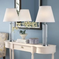 A designer's dream, this 2 table lamp set is full of unique and interesting design possibilities. Unleash your creativity by unfastening the top cap to fill the base with any decorative element of your choosing, from romantic rose petals to a coastal-inspired display of seashells, the versatile fillable base is only limited by your imagination. Resting at 28-inches in height, each of the light and airy glass cylinders is vertically book-ended by two shimmering brushed steel accents. This...