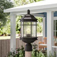 Outfit your outdoor arrangement in classic style with this one-light lantern head. Suited for wet locations, this fixture features a single 100W medium-base bulb encased within a hexagonal shade comprised of clear seeded glass panels, letting it cast a warm glow over your alfresco space. Its versatile black finish helps it blend with a variety of color palettes and aesthetics, while its cylindrical mount down below allows it to fit atop a standard 3