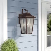 Light the way for late night guests and be welcomed home with a warm glow when you add this wall lantern to your outdoor ensemble. Crafted from metal, this piece features a scrolled arm and a tapered silhouette, lending a touch of traditional appeal to your arrangement. Four seeded glass panes diffuse light from any four compatible candelabra-base bulbs up to 60W (not included), while a wet location rating makes it ideal for your outdoor decor.