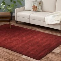 Chic and stylish, this rug is a lovely anchor for your contemporary and modern ensembles. Hand-knotted from 100% wool, it combines softness and style, making it a perfect pick for any space. The resilient fibers of this rug naturally repel stains, but they can fade in the sun and shed. This rug showcases a deep red hue, with subtle gradient variations that add depth to the piece. A rug pad is recommended.