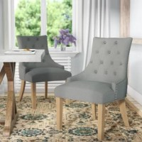 Outfit your formal dining room or eat-in kitchen in sophisticated, modern farmhouse style with this upholstered dining chair. Founded atop a solid wood base, this dapper design strikes a wingback silhouette with a high back and four legs. Neural polyester blend upholstery envelops the chair, while subtle nailhead trim and button tufting adds interest. Assembly is required. Arrives in a set of two, and each chair has a weight capacity of up to 200 lbs.