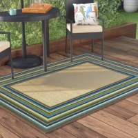 Lay a contemporary foundation for your stylish space—inside or outdoors—with this understated area rug, showcasing a solid-hued beige middle with a striped blue and green border. Made in Egypt, this rug is machine woven of stain and fade-resistant polypropylene in a low 0.16'' pile—perfect for laying out in high-traffic areas and places prone to stains and spills. Available in a curated selection of sizes to best suit your space, this rug features a woven polypropylene backing to...