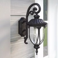Greet your guests with a warm glow before you even get to the front door with this wall lantern, perfect for any porch that wants to impress. Designed to live outdoors, it is crafted from rust-resistant cast aluminum that doesn't mind UV light shining down or a little rainstorm rolling through. Its frame is eye-catching with a scrolling arm and turned finial details, but the single light behind a seeded glass shade is what really shines.