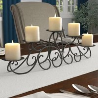 There's nothing quite like candlelight to create an ambience for festive holiday feasts and intimate dinners alike. With its curvaceous details and romantic design, this vintage iron candelabra candle holder is a charming addition to any ensemble. Crafted of wrought iron in a blackened bronze finish, this alluring design showcases a swirling scrollwork base with five round drip tray candle holders. Designed to accommodate your preferred pillar candles up to 3.5