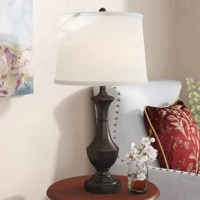 Round out your ensemble with a touch of classic style and a warm glow with this charming table lamp. A lovely addition to your master suite nightstand or entryway console, it showcases a metal design with turned details and a pedestal base. Finished with an oil rubbed bronze hue, it can pair well with any color palette from neutral to bright. It is topped with oatmeal linen drum shade and it accommodates one 150 W bulb.