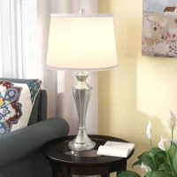 Perfect at the bedside or paired with a cozy arm chair, this table lamp introduces stylish accent lighting to any interior space. Crafted of metal and awash in a silvery brushed nickel finish, this lamp stands sleek and polished, while an artfully turned silhouette brings a touch of traditional to today. Tempering this lamp's modern side, a crisp white linen shade completes the look. This fixture accommodates a 100W bulb (not included).