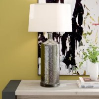 Bring sleek sophistication and a pop of glam to your ensemble with this lovely table lamp. Use it on your entryway console or set it on your nightstand to cast a warm glow over your space. The base is crafted from metal in a jar-style shape. The elegant silver finish shimmers in any space thanks to the hammered texture. It is topped with a white drum shade and measures 27.5'' H x 15'' W x 15'' D.