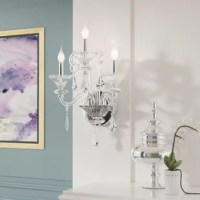 If a wall sconce and a chandelier decided to become one, you'd get this lovely light. Measuring 20'' H x 19'' W x 19'' D overall, its frame is traditional with a touch of fanciful flair, featuring curved arms and carved details. Though dripping crystal accents up the style of this luminary, what really makes it shine are the three candelabra-inspired lights, exposed for a warm glow. Though we think this design would perfectly suit a powder room, we do not recommend using it in damp areas, like...