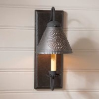 Their 1-Light Candle Wall Light is a sconce turned small wall light. With the addition of a punched tin shade, the ambience factor of this beautiful sconce is second to none. Finish is textured and lightly distressed. Black textured arms with crimped pans. Handcrafted in Pennsylvania.