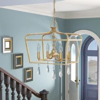 Whether illuminating the entryway or dangling over your dining room table, this posh lantern is sure to bring both styles and shine to your space. An investment for any ensemble, this luminary's frame features an openwork silhouette with a brio gold finish and hanging crystal accents for a pop of glamour. Its four candelabra-inspired lights inside are the star of this piece, creating a warm glow in traditional fashion. Measures 19.25'' H x 14.25'' W x 14.25'' D.