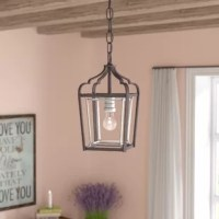 Illuminate your space in modern farmhouse style with this streamlined one-light foyer pendant. Crafted of clean-lined metal tubing in a rubbed sienna finish, this fixture features an open rectangular frame with a curvy, arched roof. A speckled pewter inner frame surrounds a matching socket within to round out the design. An adjustable length of chain suspends the unit from a matching canopy above, while a vintage A19 Edison bulb (not included) disperses bright light throughout your space.