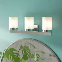 Installed above or alongside mirrors, vanity lights are purposeful fixtures that keep your bathroom looking at its best. Clean and polished, this three-light fixture sports a metal bar and backplate – both awash in chrome – and three white cylinder glass shades that take on a yellowish tint when illuminated. This vanity light accommodates 100 W incandescent or LED-equivalent bulbs (not included). Plus, it can be hung as an up or downlight to suit your specific needs.