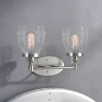 This curated, industrial two-light vanity light features an oval-shaped backplate complete with decorative screw caps, while one horizontal rod arm supports two contemporary torch-inspired glass holders. Two clear seeded glass shades ensconce 60 W incandescent Edison bulbs (not included) to disperse bright light throughout your space. UL-listed for use in damp indoor locals, this fixture can be mounted uplight or downlight according to your preference.
