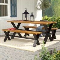 An industrial update on a classic picnic table ensemble, this three-piece set anchors your dining space in contemporary farmhouse style! The table strikes a rectangular silhouette with a solid acacia wood top in a rich, natural wood grain finish, while a powder-coated, x-frame trestle base lends some eye-catching appeal. Rounding out this design, the accompanying two benches allow room for up to six people.