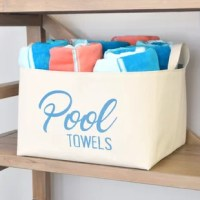 Stack your pool towels in this stylish extra large canvas storage bin, featuring charming typography in caribbean blue.
