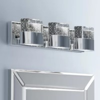 Illuminate your powder room in eye-catching and modern style with this three-light bath bar. Crafted of metal in a gleaming chrome finish, this fixture features a clean-lined rectangular backplate accented with a reflective rain glass panel, while three short square arms secure oval-shaped pendant holders in place. Three oval-shaped rain glass shades round out the design, diffusing bright light throughout the room. This luminary is rated for damp locations, perfect for bathrooms with steamy...