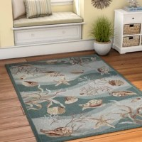 Whether your abode is beach-side or a little more landlocked, you can bring in a splash of sea-worthy style with this eye-catching area rug. Showcasing a seashell and coral motif with a wavy seafoam pattern, this piece is perfect for adding whimsy and nautical charm to your ensemble. Hand-hooked from polyester, this design offers a low 0.25'' pile height for a look that's both casual and easy to clean. To keep it safely in place, we recommend using with a rug pad.