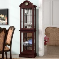 Put a collection of antiqued curios on display or simply organize your serveware for dinner parties and festive family feasts with this cabinet. Standing 73.6'' tall, its frame is crafted from solid and manufactured wood with a cherry finish. The rounded top is accented by a traditional clock accent, while each of the six shelves inside are given depth and dimension with a mirrored back. Assembly for this product is required.
