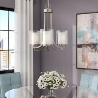 Bring a boost of brightness and a dash of contemporary style to any space in your home with this three-light chandelier. Crafted from metal, this fixture features an adjustable hanging chain and an open frame with curved arms in a brushed nickel finish for a sleek touch. Etched white frosted glass inner shades and clear glass outer shades round out the design and create a layered look, while compatible 100 W medium-base bulbs (not included) sit within to offer up a warm glow.