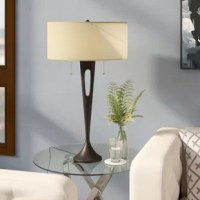 Update any end table in a pinch with this eye-catching table lamp. Showcasing a bronze finish and topped with an off-white drum shade, its column stands gently tapers down to a wider, balanced base. Its neutral colors and understated design adapt to aesthetics ranging from contemporary to transitional. Measuring 31'' H, its substantial height ensures it stands out in your home. Insert two 60 W bulbs (not included), and pull the chains to turn each one on and off.