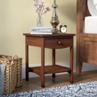 Available in a curated selection of classic finishes, this nightstand is crafted of solid tropical woods with laminates, striking a clean-cut and curved silhouette. A slide-out drawer offers out of sight storage for reading glasses, a book light, or other bedside essentials, while an open lower shelf is perfect for storing a basket of throw blankets or a box of tissues. Rounding out the design, the smooth tabletop provides an ideal platform for a table lamp and a framed photo.