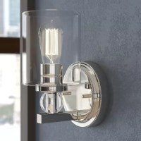 Brighten up your powder room in curated, contemporary style with this chic one-light bath sconce. Crafted of metal in a polished nickel finish, this fixture features a circular backplate with traditional moldings and decorative screw caps, while one short, square art juts out from its lower half. A streamlined, cylindrical socket sits on a clear crystal glass orb for a touch of sculptural style, while a clean-cut cylindrical glass shade ensconces one 60 W Edison bulb (Not included) to disperse...