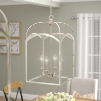 Illuminate your kitchen, dining room, or entryway in modern farmhouse style with this four-light foyer pendant. Crafted of clean-lined, tubular metal in a luxe finish, this fixture's frame strikes an open rectangular silhouette with clear glass panel sides and a cathedral dome roof. Inside, four candle-style lights accommodate 60 W E12 candelabra bulbs to spread bright light throughout your space. Rounding out the design, an adjustable length of chain suspends the unit from a matching canopy...