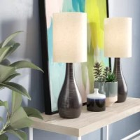 Lightening up your space, doesn't mean sacrificing style for boring fixtures. Table lamps can be just as eye-catching, and statement-making, as a piece of art on your wall. Take this lamp as an example, it features a distinctive vase-shaped body, and is perfectly suited for modern-inspired aesthetics. Arriving as a matching set of two, it is crafted from metal, in a dark bronze finish, with a fabric drum shade on top. Each lamp accommodates one compact fluorescent lightbulb, of up to 13 W...