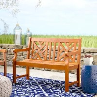 Traditional, yet relaxed, this wooden garden bench is an excellent addition to your outdoor ensemble. Crafted of solid eucalyptus wood responsibly sourced from Brazil, this garden bench showcases a gently-slanted backrest, two curved, fixed arms, and a four-legged trestle base. The backrest showcases an openwork trellis motif, while the bench seat is slatted so rain falls right through. Measuring 35