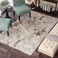 Set a contemporary foundation for your stylish space with this beige and gray area rug, showcasing an abstract floral motif in watercolor hues. Made in India, this area rug is hand-tufted from 100% wool in a thick 0.63