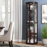 Put a spotlight on stylish serveware or artful accents with this lighted curio cabinet, complete with compatible 25 W halogen bulbs to cast light downward on the four glass interior shelves. Crafted from poplar wood with veneers in a versatile dark chocolate cherry finish, this design features clear glass sides and a mirrored back to help scatter light around your space. With a slender and rounded silhouette measuring just 72'' H x 22'' W x 12'' D, this compact piece is a fine fit for narrow...