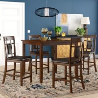 Whether enjoying an everyday meal with the fam or casually catching up with close friends over cocktails on the weekend, this five-piece counter height dining set is a must-have for your abode. Crafted from manufactured wood with solid veneers, the table showcases an understated design with four tapered legs and a brown finish. Four matching chairs with an open back and faux leather upholstery complete the look and let you dine in style!