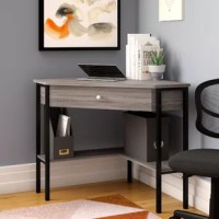 Turn any corner into your home office or study space with this corner unit writing desk! Crafted of manufactured wood with laminate veneers, this desk strikes a wedge-shaped silhouette in a rustic gray-wash finish for a reclaimed look, while five black metal legs lend an industrial touch. Set on soft-close glides, a center drawer offers out-of-sight storage for office supplies and accessories, while an L-shaped lower shelf is great for stowing folders, files, and books. Measures 30