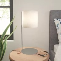 Bring a touch of modernity to the master suite while illuminating your latest bedside read with this table lamp. Founded atop a thin, circular base, its metal frame sports a polished steel finish for a sleek appearance, highlighted up top by a frosted glass shade. Its drum shade evenly casts the glow of one 13 W bulb (not included) over your ensemble. Measures 18.5'' H x 8'' W x 8'' D.