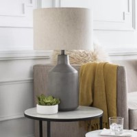 Perfect for adding a touch of style while they light up a room, table lamps are versatile, space-conscious lighting fixtures – and we can't get enough of them! Take this one, for example: crafted from a concrete base with a vase-like silhouette and marbled finish, this piece is a great option for an understated accent in any ensemble. A linen drum shade caps this piece off with understated style perfect for ensembles from modern farmhouse to contemporary. This lamp accommodates a single 100 W...