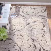 Add a layer of plush softness and elegant design to your floors with this shag area rug. Featuring an elegant, wandering scroll pattern, this rug is constructed with an extreme high-low cut and loop pile for lavish comfort underfoot. Neutral hues accentuate the carving-like motif of this rug that's sure to enhance any room. Made with high-quality frieze polypropylene yarns, this rug has a cushion-like texture and offers a welcoming look and feel.