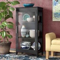 """""""My home has too much storage space,"""" said no one ever. The truth is, we can always use a little extra organization for our things. Here to help, this Curio cabinet brings both storage and display space to your dining room. It features one glass cabinet door, with three interior shelves behind it, to store all your favorite pieces of China, plateware, and decorative accents. This piece is constructed of manufactured wood, with a black finish, and clear glass – making it perfect for..."""